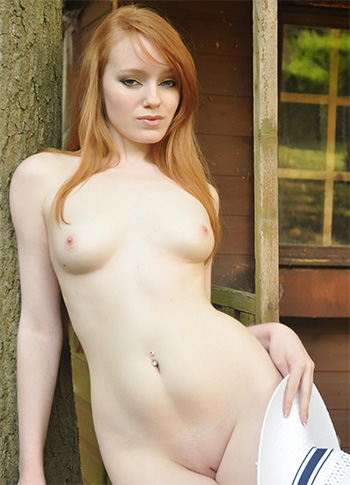 Young skinny redhead in a hat shows her small tits and clean pussy